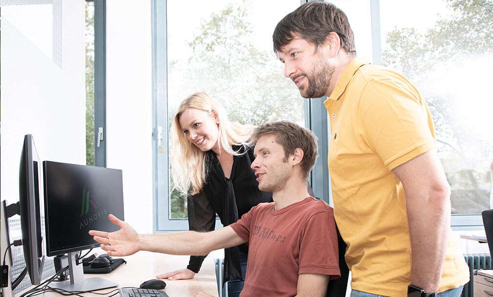 AUNOVIS Gruppenbild Entwickler am Arbeitsplatz